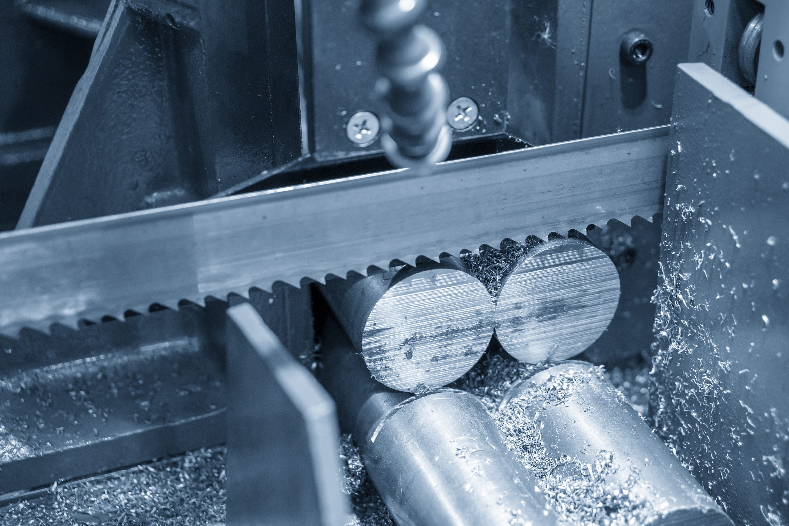 The  band saw machine cutting raw metals rods .The industrial sawing machine cutting the material rod.